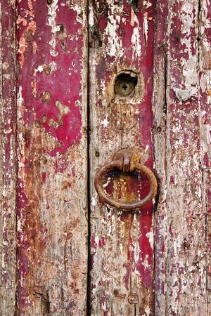 doorhandle: Old grungy wooden door with peeling paint and rough door-handle