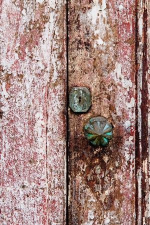doorhandle: Old grungy wooden door with peeling paint and round door-handle Stock Photo