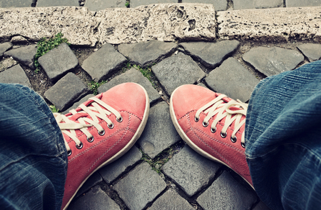 choise: Feet in red sneakers and jeans outdoors. Choise of the way. Stock Photo