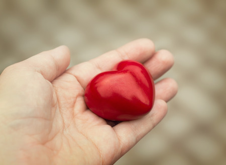 Young woman holds out a red heart in her hand, concept of love, kindness and empathy