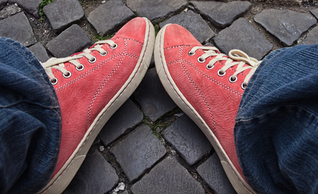first step: Feet in red sneakers and jeans outdoors. Making first step. Stock Photo