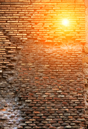 lopsided: Red brick wall with  lop-sided rustication, texture grunge background, sun shoot through wall Stock Photo