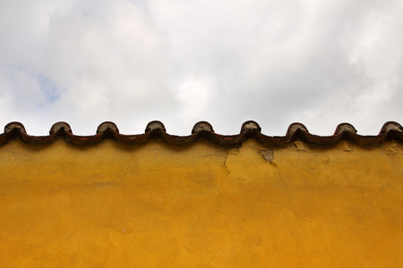 Roof and wall of the old house on clouds background Stock fotó