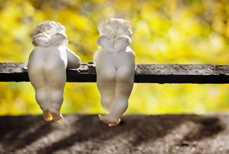 Funny white ceramic angels with small wings are back view in autumn park. Stock Photo