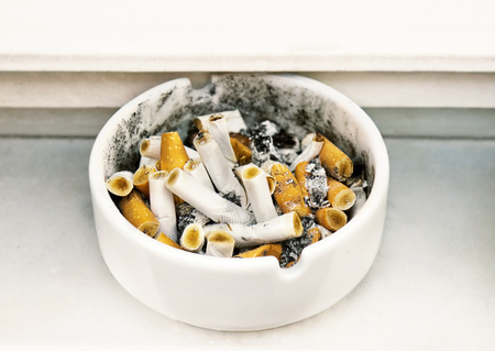 Cigarette butts in a ceramic ashtray, smoking in public places.