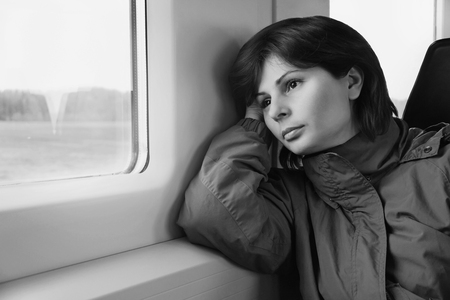 Young woman is traveling by train, looking to the window