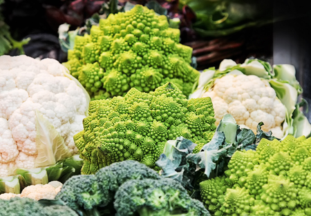 Different kinds of cabbage (Romanesco, broccoli, cauliflower) in a basket at market.