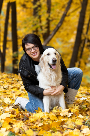 Beautiful smiling brunette woman with golden retriever in autumn park.