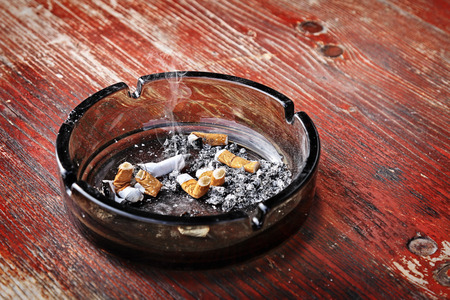 Cigarette butts in a glass ashtray on shabby wooden table, pernicious habits.