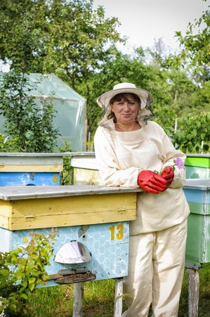 Portrait of a woman beekeeper with a flower in her hand