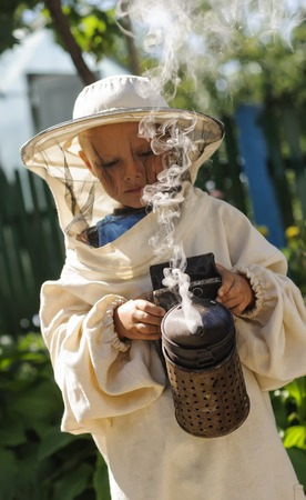 smoker: Young farm beekeeper boy using a smoker on bee yard