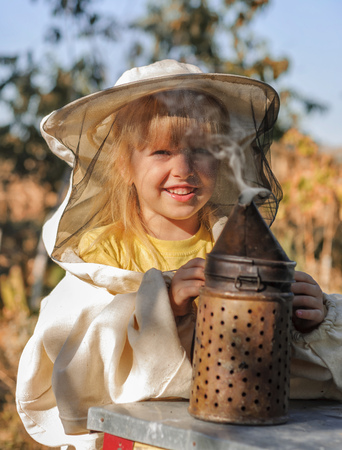 smoker: Little girl beekeeper blows smoker for bees.