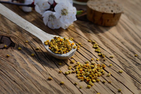 Grains of bee pollen in a wooden spoon on wooden table. Apitherapy. Bee products