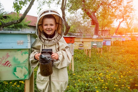 The boy in protective clothing beekeeper works on an apiary. Apiculture.