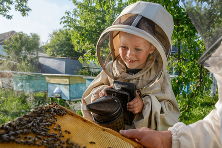 teaches: Experienced beekeeper grandfather teaches his grandson caring for bees. Apiculture. The concept of transfer of experience