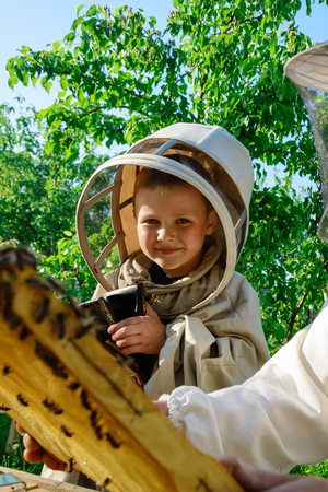 A boy wearing a protective suit in an apiary near a hive with bees.