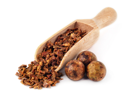 Beet propolis granules in a wooden spoon are isolated on a white background. Natural antibiotic. Beekeeping product. Apitherapy.