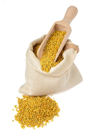 Flower bee pollen in a bag with a wooden scoop isolated on a white background. A natural source of vitamins and minerals. Beekeeping products. Apitherapy. Stock Photo
