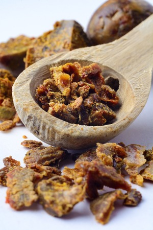 Propolis granules in a wooden spoon. Bee glue. Bee products. Apitherapy. Apiculture.