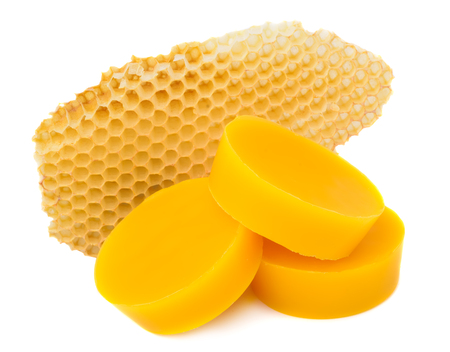 Pieces of natural beeswax and a piece of honey cell are isolated on a white background. Beekeeping products. Apitherapy.