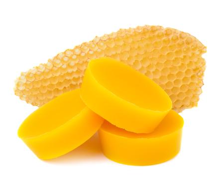 Los pedazos de cera de abejas natural y un pedazo de célula de miel están aislados en un fondo blanco. Productos apícolas. Apiterapia