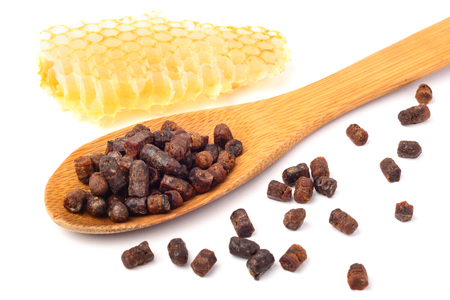 Granules of bee bread in a wooden spoon and a honeycomb are isolated on a white background. Apitherapy. Beekeeping products. Strengthening immunity. Stock Photo
