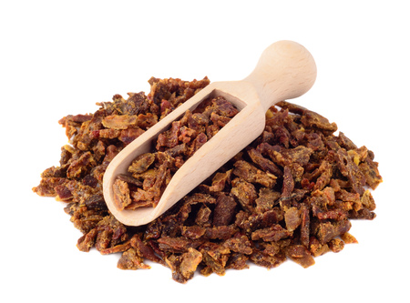 Propolis granules in a wooden shovel are isolated on a white background. Bee glue. Bee products. Apitherapy