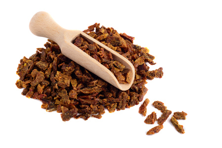 Propolis granules in a wooden shovel are isolated on a white background. Bee glue. Bee products. Apitherapy. Stock Photo