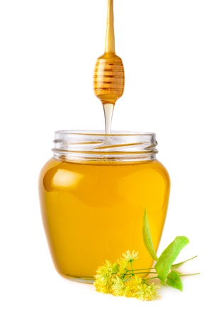 Glass jar of fresh linden honey with flowers of linden on white. Stock Photo