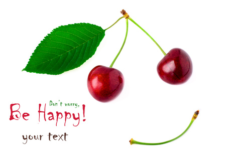 Two red cherries with a yellow green leaf on a white background. Smile concept. Dont worry Be Happy.