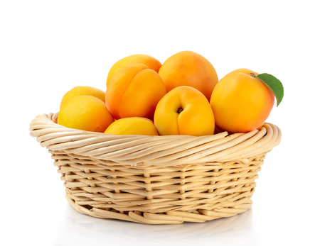 Fresh apricots in the basket are isolated on a white background. Archivio Fotografico