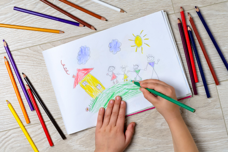The child draws his family on a piece of paper with colored pencils. What can a childrens picture tell. The concept of child psychology. Stock Photo