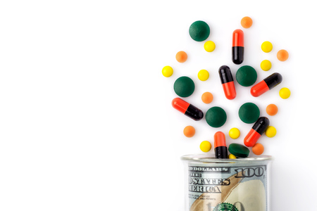 Colorful pills spilled from a bottle made of money, on white background. The Concept of Drug Purchase. 免版税图像