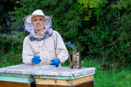 Portrait of a beekeeper in an apiary near a hive in a protective suit. Beekeeping concept. Beekeeper harvesting honey.