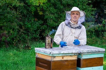 Portrait of a young beekeeper in an apiary near a hive in a protective suit. Beekeeping concept. Beekeeper harvesting honey. Stock Photo