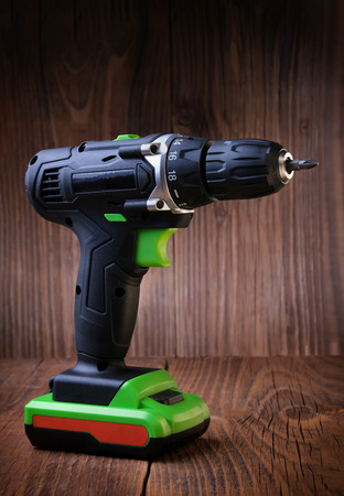Electric screwdriver on rustic wooden background. cordless drill. maintenance home concept. Space for text.