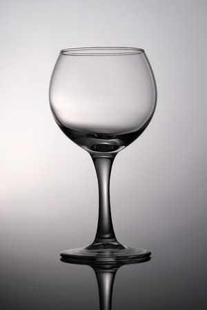 Black and white photograph is an empty glass for wine on a gray gradient background.