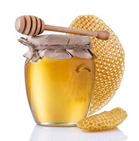 Glass jar full of honey and wooden stick on a white background. Reklamní fotografie