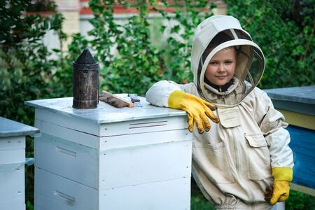 Boy beekeeper in apiary near beehives.Honeycomb with honey. Organic food concept. The most useful organic honey.