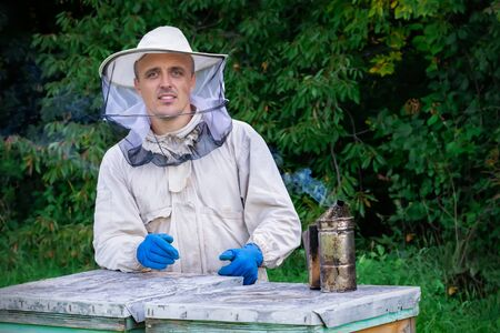 Young beekeeper working in the apiary. Professional beekeeper working outdoors and wearing the protective suits used for beekeeping. Beekeeper harvesting honey from a bee hive.