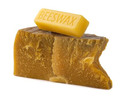 Trozos de cera de abejas orgánica sobre un fondo blanco. El uso de cera de abejas en apiterapia. Ingrediente de producción para uso médico y cosmético.