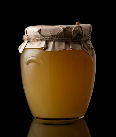 Glass jar with honey isolated on black background. Organic honey.