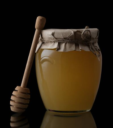 Sweet honey in jar with honey dipper on black background. Organic honey.