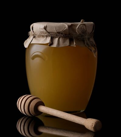 Sweet honey in jar with honey dipper on black background. Organic honey. Standard-Bild - 142073968