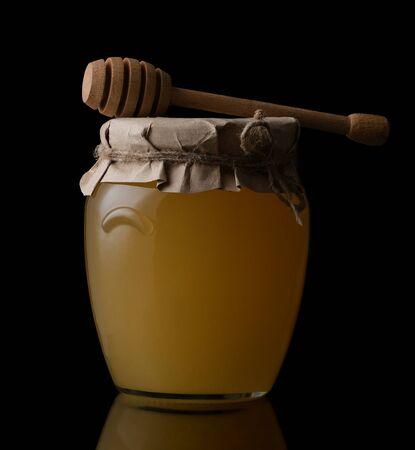 Sweet honey in jar with honey dipper on black background. Organic honey Reklamní fotografie