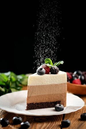 Piece of light mousse cake with fruits on on wooden surface. Mousse cake recipe for three chocolates.