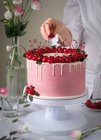 Cake with cherry. The confectioner decorates the cake.