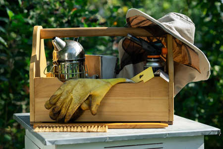 A tool of the beekeeper. Everything for a beekeeper to work with bees. Smoker, a chisel, a box, beekeeper suit for protection from the bees. Beekeeping equipment. Photo on the topic of beekeeping.