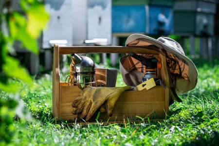 A tool of the beekeeper. Everything for a beekeeper to work with bees. Smoker, a chisel, a box, beekeeper suit for protection from the bees. Beekeeping equipment. Beekeeping concept. Stock Photo