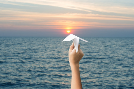 plane paper in children hands and sunset, forward to the target concept.